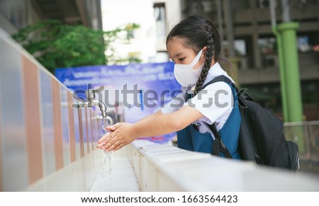Asian student  washing hands at the outdoor wash basin in the school. Preventing Contagious diseases, Plague. Kids health, protecting the virus Covid - 19 , Saving water, Cleaning, Running water. #1663564423