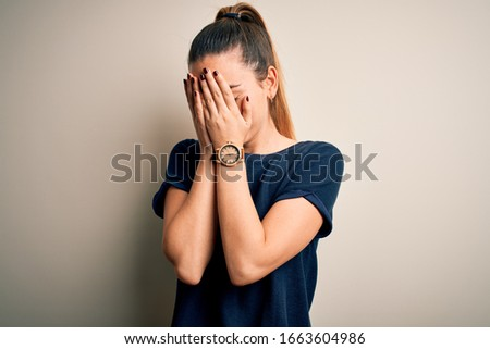 Young beautiful blonde woman with blue eyes wearing casual t-shirt over white background with sad expression covering face with hands while crying. Depression concept. #1663604986