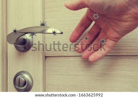 human life through which germs and viruses spread, door handle in an apartment in a room or house with hand and finger, the concept of germs sitting on the door handle #1663625992