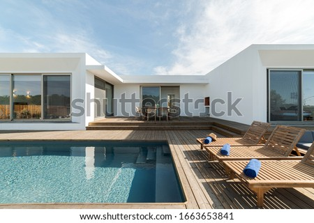 Wooden lounge chairs in modern villa pool and deck #1663653841