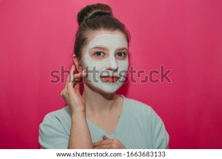 Young beautiful girl with big blue eyes smiling hands near face, with a white clay mask on her face and hair bumps on a pink background  #1663683133