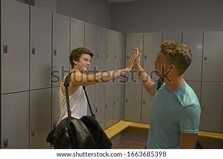 Teenage boys hi-fiving in gym locker room #1663685398