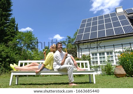 Couple eating iced lollies in garden of solar paneled house #1663685440