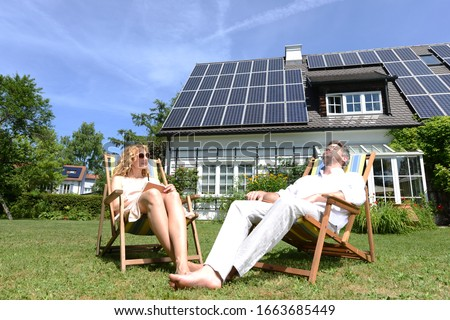 Mid adult couple in deckchairs in garden of solar paneled house #1663685449
