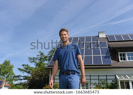 Portrait of man in garden of solar paneled house Royalty-Free Stock Photo #1663685473