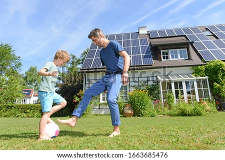 Father and son playing football in garden of solar paneled house #1663685476