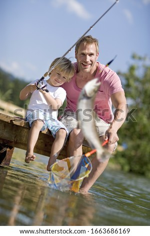 Father and young boy on jetty fishing #1663686169