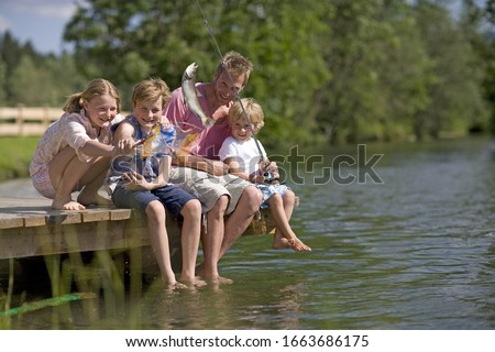 Father and children on jetty fishing #1663686175