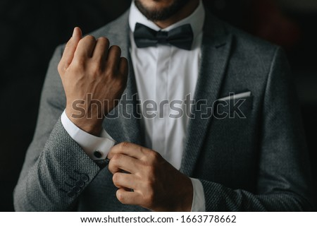 the groom fastens the cufflinks at the groom's morning gatherings #1663778662