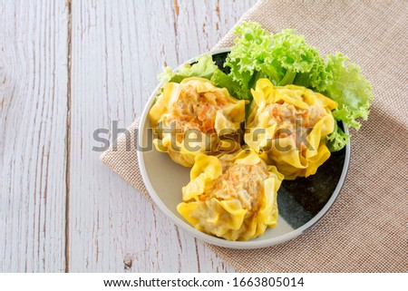 Chinese Steamed Dumpling, Shumai on white dish served with soy sauce and lettuce leaves on brown cloth and wooden table. Delicious Dimsum pork. #1663805014