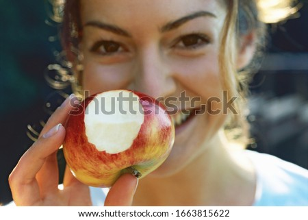 Young woman holding apple with bite out of it #1663815622