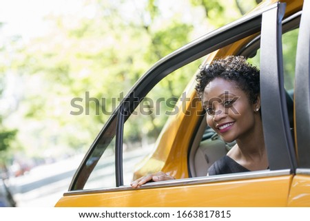 City life. People on the move. A woman getting out of the rear passenger seat of a yellow cab. #1663817815