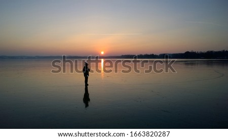 Boy walking on frozen Lake Woerthsee at sunset, Bavaria, Germany, Europe #1663820287