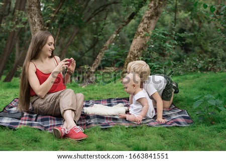 Young beautiful mother is taking pictures of their children on phone. Mom and two children on picnic