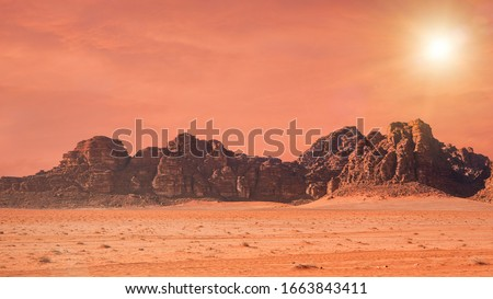 Planet Mars like landscape - Photo of Wadi Rum desert in Jordan with red colour filter and added sun, this location was used as set for many science fiction movies #1663843411