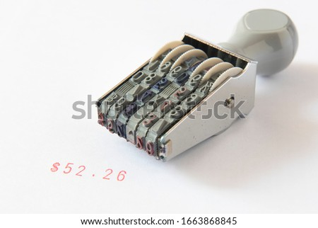 Old rubber stamp, used office equipment, then put on white paper There is a $ 25.26 number text and a red message, earning money and urgently needing money, or working to make money. #1663868845