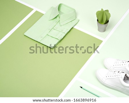 Mint green plain cotton formal shirt, white sneakers and artificial succulent arranged on a various green paper background. Trendy work outfit or minimalist office concept background with copy space. #1663896916