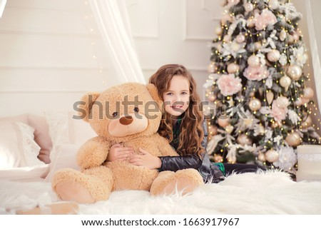 Happy funny child girl on the bed against the background of a Christmas tree with a big polar bear toy. Little girl picture in the New Year decorations. New Year's advertising.