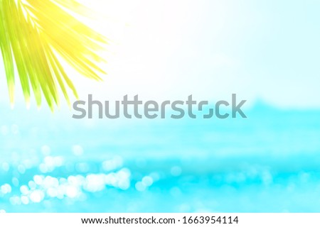 Blur beautiful nature green palm leaf on tropical beach with bokeh sun light wave abstract background. Copy space of summer vacation and business travel concept. Vintage tone filter effect color style #1663954114