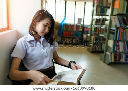 Teen girl reading in library or study room, young learner reading books in the corner of library in school, college, or university campus, educational or academic concept picture of student studying