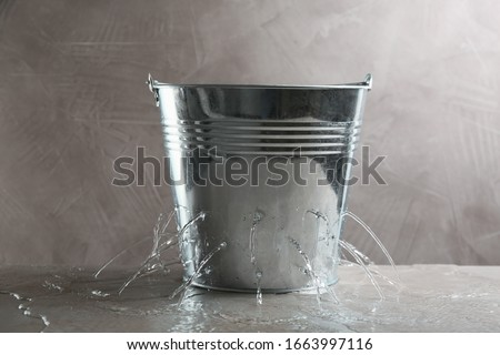 Leaky bucket with water on table against grey background #1663997116