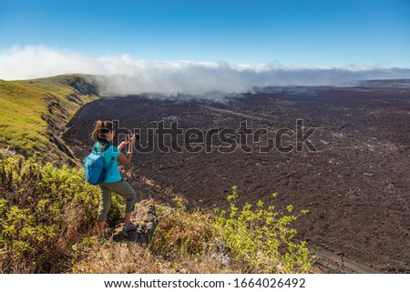 Galapagos tourist hiking on volcano Sierra Negra on Isabela Island taking photos with camera. Woman on hike on famous landmark, worlds 2nd largest active volcanic caldera, Galapagos Islands Ecuador.
