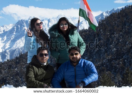 Stylish men and women enjoying ski holiday, Friends in warm clothing with Indian flag on snowy mountain landscape #1664060002