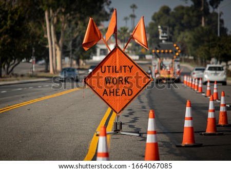 Traffic sign with flags reading Utilitary Work Ahead with traffic cones on road with electronic arrow pointing to the right to divert traffic Royalty-Free Stock Photo #1664067085