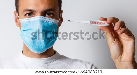 Coronavirus. 2019 Novel Coronavirus (2019-nCoV), Wuhan, China. A man with Coronavirus reads his temperature on a thermometer. Isolated on white. Room for text. Clipping Path. #1664068219