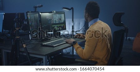 Medium shot of a wheelchaired film editor working on a movie