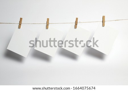 Empty paper frames that hang on a rope with clothespins and isolated on white. Blank cards on rope. Mockup template for memories backdrop, photos, social media etc. #1664075674