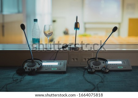 Inside of translation or  interpreting booth. Desk with microphones and audio board, with visible conference hall in the background.