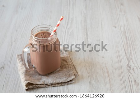 Homemade New England Chocolate Milkshake in a Glass Jar Mug on a white wooden background, low angle view. Copy space. #1664126920