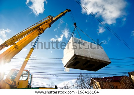 Industrial Crane operating and lifting an electric generator against sunlight and blue sky Royalty-Free Stock Photo #166416104