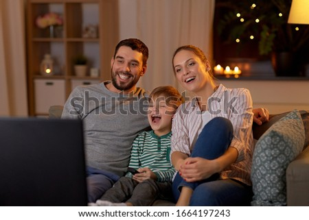 family, leisure and people concept - happy smiling father, mother and little son with remote control watching tv at home at night #1664197243