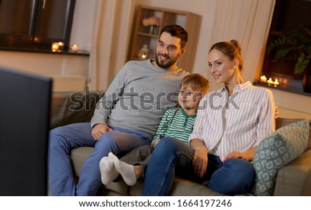 family, leisure and people concept - happy smiling father, mother and little son with remote control watching tv at home at night #1664197246