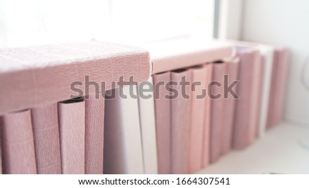Large stack of books on windowsill. Books wrapped in colored paper lie on window sill. #1664307541