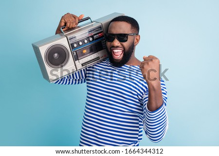Photo of funny dark skin guy hold retro cassette recorder on shoulder raise fist amazing students party chill wear sun glasses striped sailor shirt isolated blue color background #1664344312