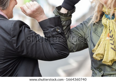Elbow bump. New novel greeting to avoid the spread of coronavirus. Two women friends meet in a British street and instead of greeting with a hug or handshake, they bump elbows instead. #1664360740