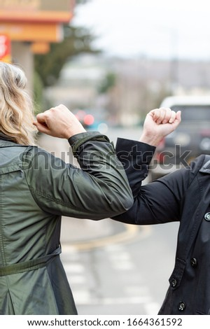 Elbow bump. New greeting to avoid the spread of coronavirus. Two women friends meet in British street with bare hands. Instead of greeting with a hug or handshake, they bump elbows instead. Vertical. #1664361592
