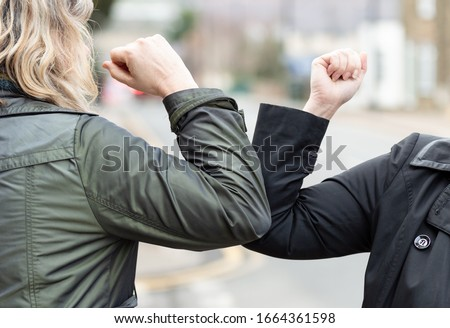 Elbow bump. New novel greeting to avoid the spread of coronavirus. Two women friends meet in a British street with bare hands. Instead of greeting with a hug or handshake, they bump elbows instead. Royalty-Free Stock Photo #1664361598