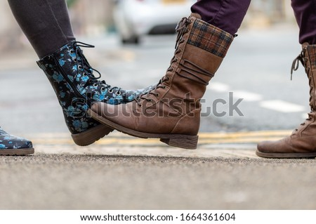 Foot tap. New novel greeting to avoid the spread of coronavirus. Two women friends meet in a British street. Instead of greeting with a hug or handshake, they touch their feet together instead. #1664361604