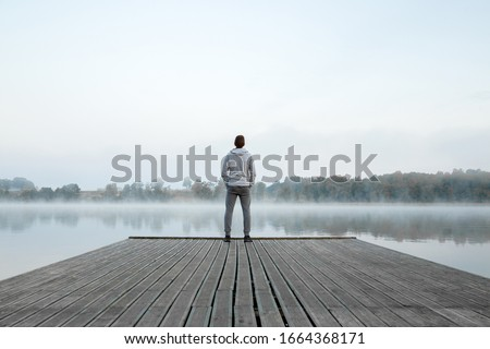 Young man standing alone on wooden footbridge and staring at lake. Thinking about life. Mist over water. Foggy air. Early chilly morning. Peaceful atmosphere in nature. Enjoying fresh air. Back view. #1664368171