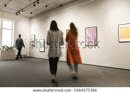Exhibition in modern crowded art gallery Royalty-Free Stock Photo #1664375386