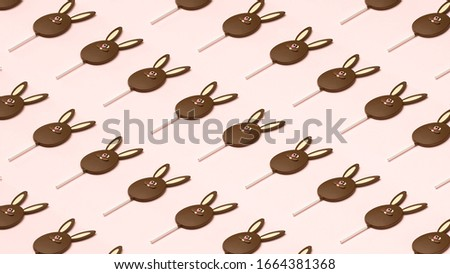 Easter bunny made of chocolate, isometric pattern composition, top view image. Creative chocolate rabbit concept, pink pastel table background, sweet dessert eggs flat lay modern minimalist decoration