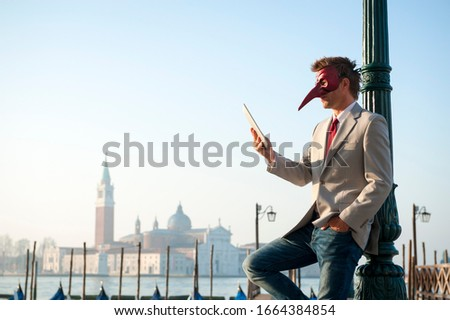 Man wearing Venetian carnival mask standing outdoors using a tablet in a plaza in Venice, Italy #1664384854