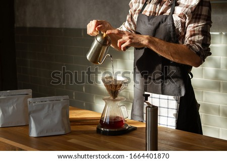 Coffee shop worker standing at the counter with hand drip coffee set Royalty-Free Stock Photo #1664401870