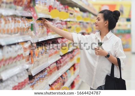 Consumer  shopping  supermarket stores  department stores goods,Asian women are shopping at the supermarket in the mall. And as a good consumer Car selection of quality products  Royalty-Free Stock Photo #1664424787