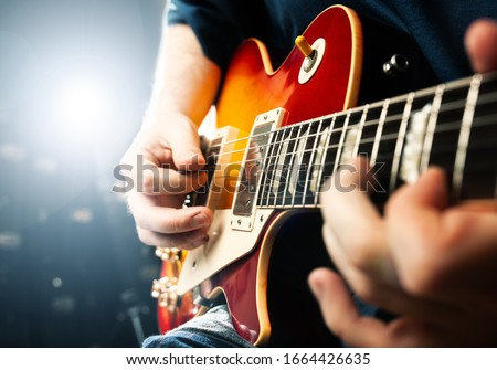 man playing on guitar, stage light, musical concert close up view Royalty-Free Stock Photo #1664426635