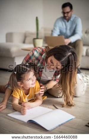 Mom is always there to help. Little girl working her homework with mother. Focus is on foreground. #1664460088